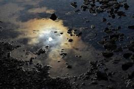 cielo con sole che si specchia in pozza d'acqua
